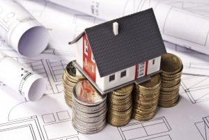 Miniaturhaus auf gestapeltem Geld
